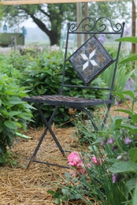 A simple iron chair resting in the garden